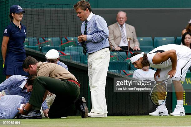 Spanish tennis player Rafael Nadal looks on as officials and medical staff attend to a linesman who has fainted on Centre Court during play in the...