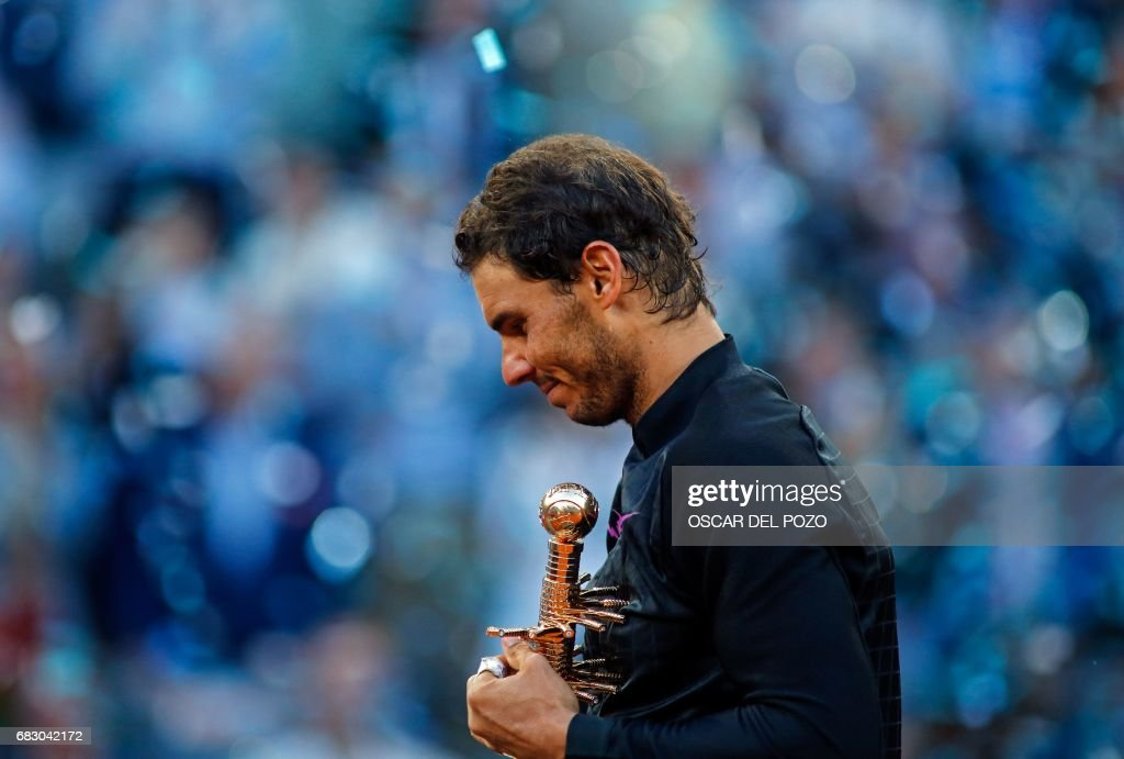 Spanish tennis player Rafael Nadal poses with his trophy as he celebrates his victory over Austrian tennis player Dominic Thiem at the end of their ATP Madrid Open final match in Madrid, on May 14, 2017. Nadal won 7-6 and 6-4. /