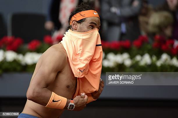 Spanish tennis player Rafael Nadal puts a shirt on during his match against Portuguese tennis player Joao Sousa during the Madrid Open tournament at...