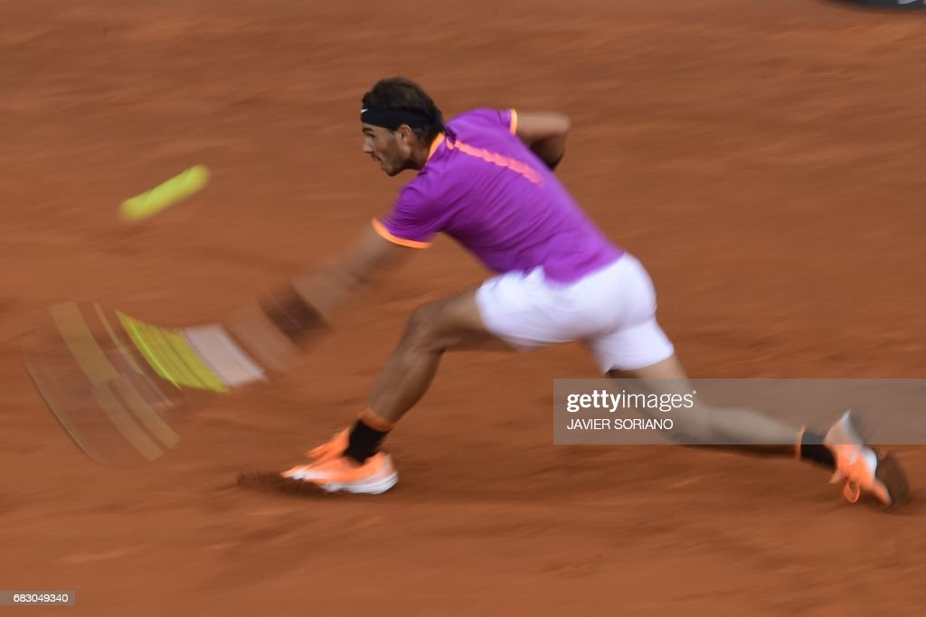 Spanish tennis player Rafael Nadal returns a ball to Austrian tennis player Dominic Thiem during their ATP Madrid Open final match in Madrid, on May 14, 2017. Nadal won 7-6 and 6-4. /