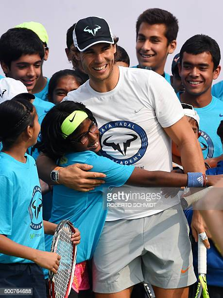 Spanish tennis player Rafael Nadal smiles as he is hugged by Indian Junior Tennis player Sandeepti Sing after she and others participated in a tennis...