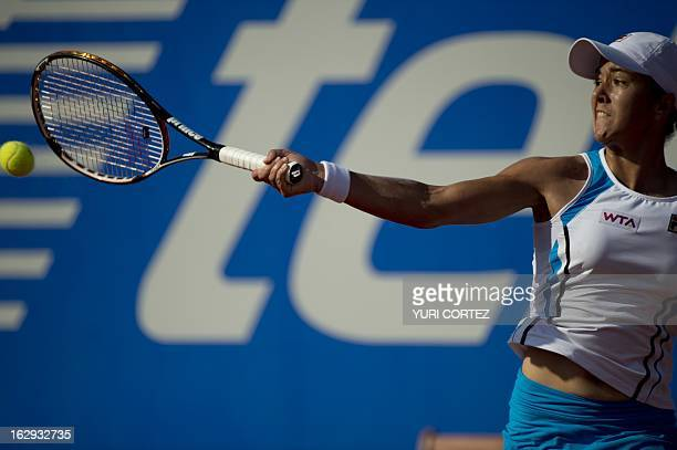 Spanish tennis player Silvia Soler hits a return to compatriot Carla Suarez during their WTA Mexican Open semifinal match in Acapulco Guerrero State...