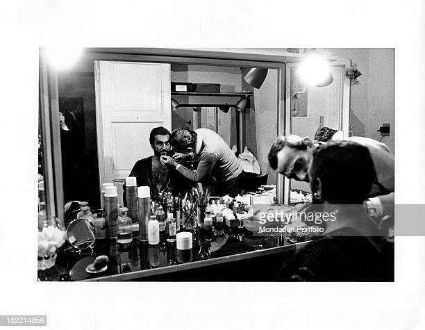 Spanish tenor and conductor Placido Domingo getting ready to play Othello in his dressing room A makeup artist gives his lips the finishing touches...