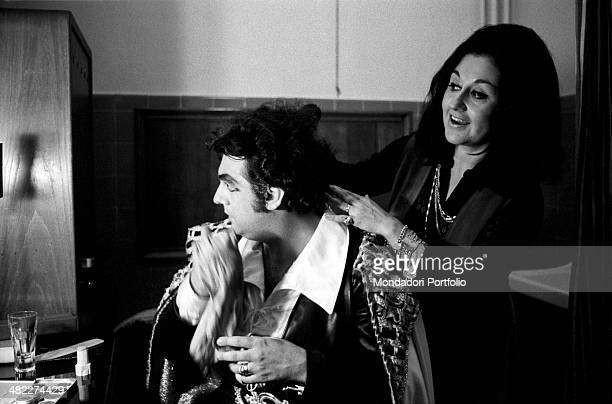Spanish tenor and conductor Placido Domingo making up in his dressing room in front of his wife and Mexican soprano Marta Ornelas. 1970s
