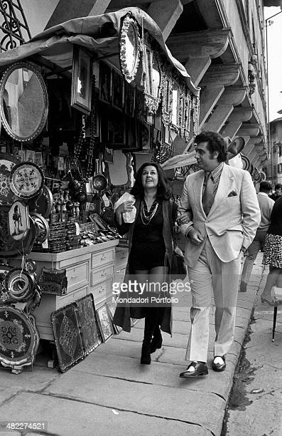 Spanish tenor and conductor Placido Domingo walking beside a stall arm in arm with his wife and Mexican soprano Marta Ornelas Florence 1970s