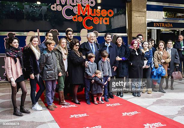 Spanish tenor Placido Domingo and his family pose with his wax figure during its presentation on January 23 2016 in Madrid Spain