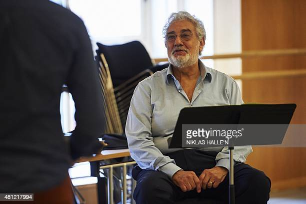 Spanish tenor Placido Domingo instructs French tenor Julien Behr during a rehearsal at the Royal Opera House in London on July 17 2015 Waving his...