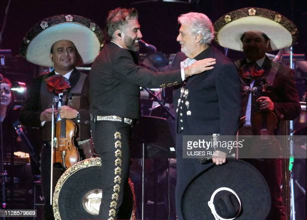 Spanish tenor Placido Domingo performs on stage with the Mexican singer Alejandro Fernandez during a concert at the Estadio 3 de Marzo stadium in...