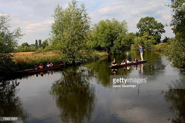 Spanish tourists relax in a punt alongside the bank of the Cherwell river while another boat heads down river as sunny weather and receding flood...