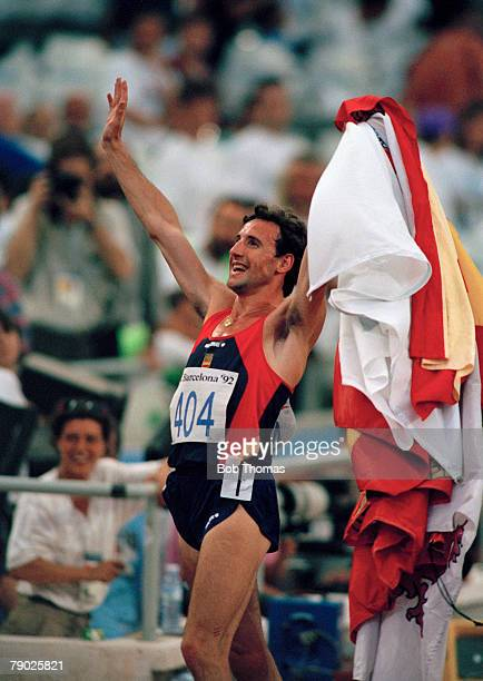 Spanish track athlete Fermin Cacho celebrates with his national flaga after crossing the finish line in first place to win the gold medal in the...