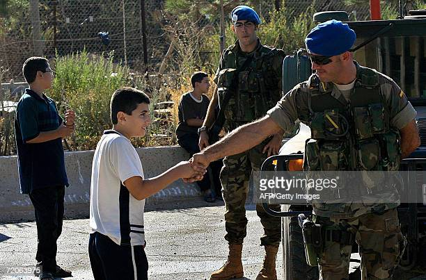Spanish UN soldier shakes hands with a Lebanese boy in the village of Kfar Kila at the border with Israel 02 October 2006 Lebanon deployed its army...