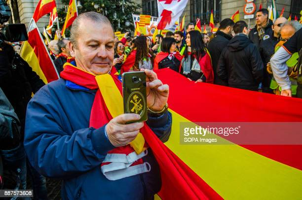 Spanish unionist protester makes photographs with his mobile phone of a large Spanish flag Spain celebrates today the 39 anniversary of its...