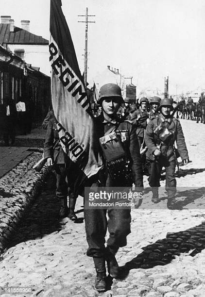 Spanish volunteers of the 'Blue Division' incorporated into the Wehrmacht on the Russian front marching with the flag of the unit September 1941