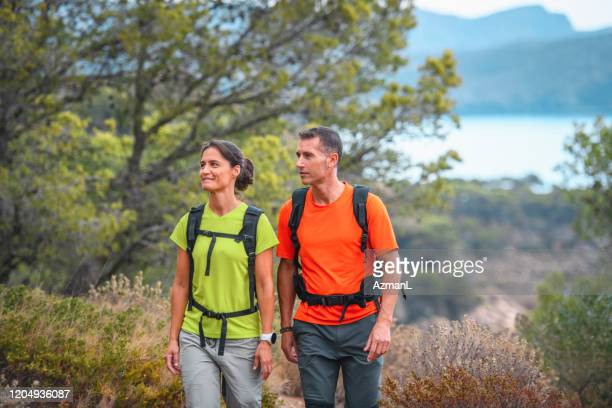 spanish weekend hikers walking in coastal tree area - mediterranean sea stock pictures, royalty-free photos & images
