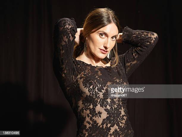 Spanish woman in black netted dress against black background, portrait