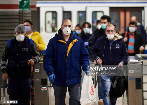 Spanish workers wear masks leaving the subway on April 13 2020 in Madrid Spain More than 15000 people are reported to have died in Spain due to the...