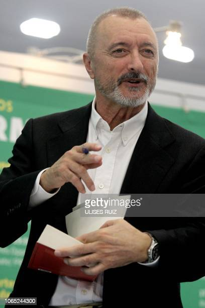 Spanish writer Arturo PerezReverte signs autographs to his readers during a book signing event during the Guadalajara International Book Fair in the...