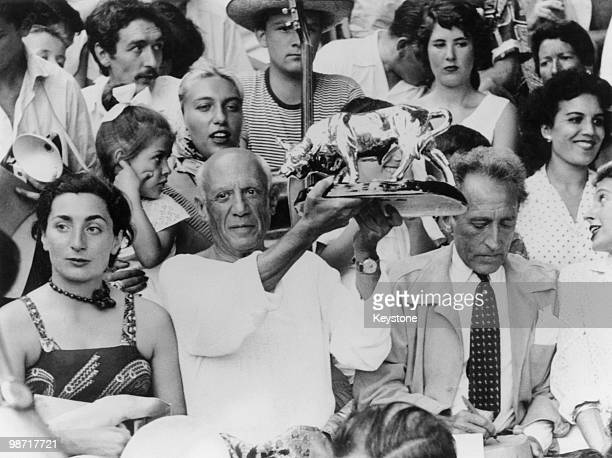 Spanishborn artist Pablo Picasso holds up a statuette of a fighting bull presented to him by toreadors in appreciation of his art in the stands at a...