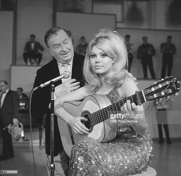 Spanish-born bandleader Xavier Cugat looks at his wife and compatriot, the musician and comedian Charo, as they appear on the CBS variety program...