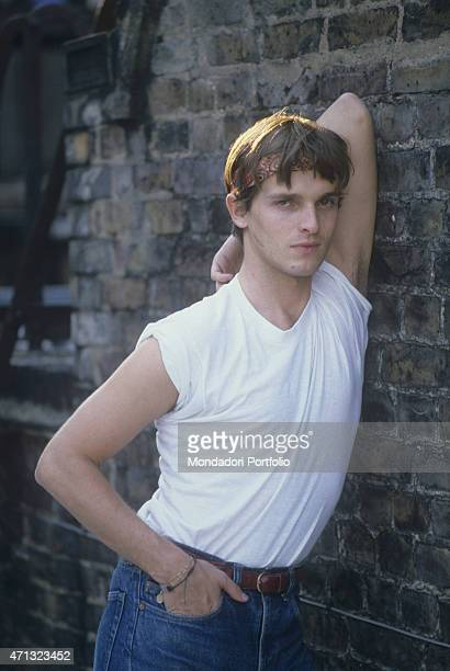 Spanishborn Italian singer and TV presenter Miguel Bos posing in jeans and bandana leaning against a wall London 1981