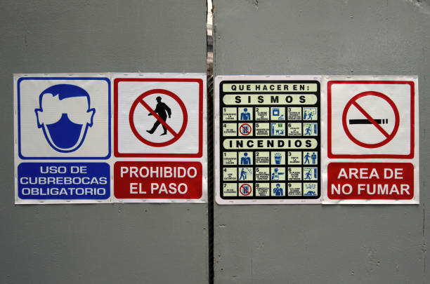 Spanish-language health and safety signage addressing covid, trespassing, earthquakes, fires and not smoking, on a construction site barrier