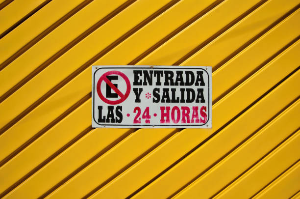 Spanish-language no parking sign on a metal fence stating 'Entrada y salida las 24 horas' [Entry and exit 24 hours]