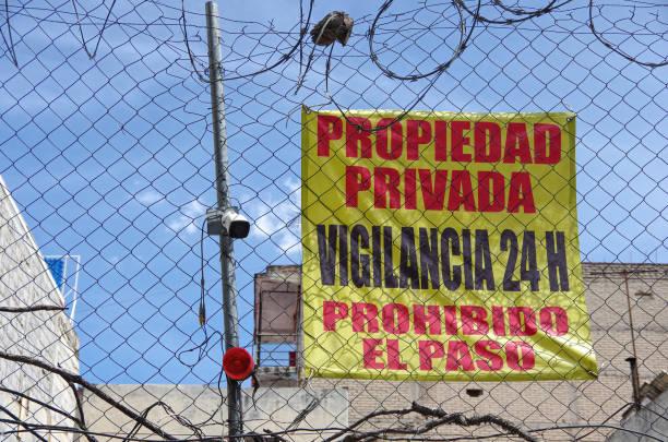 Spanish-language 'Propiedad privada. Vigilancia 24 h. Prohibido el paso' [Private property. 24 hr surveillance. No trespassing] banner/sign behind a chainlink fence