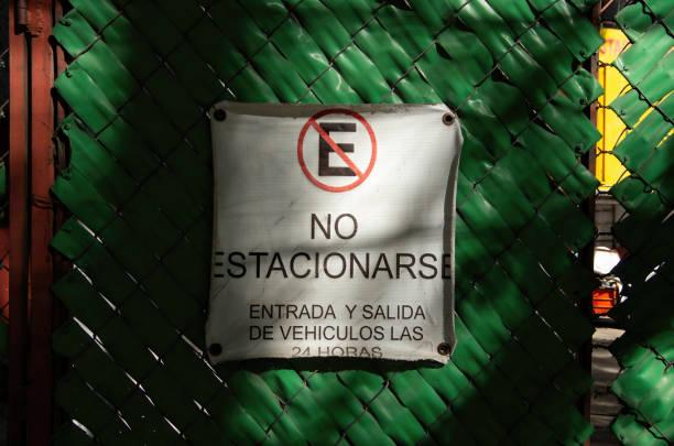 Spanish-language sign on a chainlink gate stating 'No estacionmiento. Entrada y salida de vehículos las 24 horas' [No parking. Vehicle entry and exit 24 hours a day]