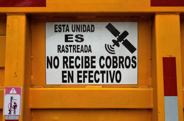 Spanish-language sign on the tailgate of a truck stating 'Esta unidad es rastreada no recibe cobros en efectivo' [This unit is tracked and does not receive cash collections]