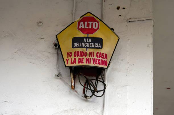 Spanish-language sign stating 'Alto a la delincuencia. Yo cuido mi casa y la de mi vecino' [Stop crime. I take care of my house and my neighbor's] on a building exterior wall