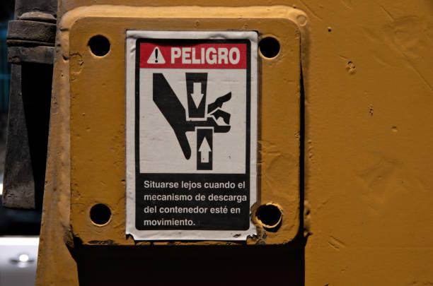 Spanish-language warning sign on heavy machinery stating 'Situarse lejos cuando el mecanismo de descarga del contenedor esté en movimiento' [Stand clear when the container unloading mechanism is in motion]