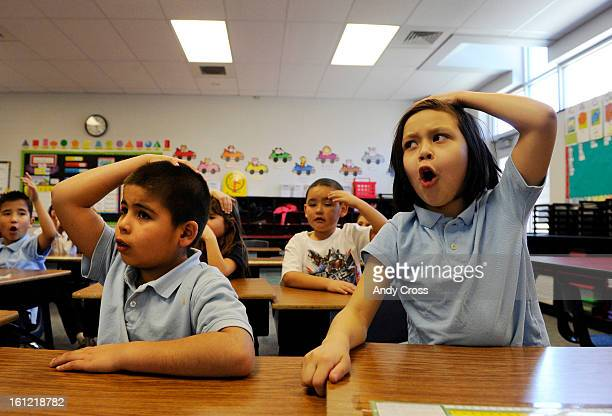 Spann Elementary School students Christian Rodriguez left and Lilian Martinez right put their hands on the heads to signal that they know the answer...