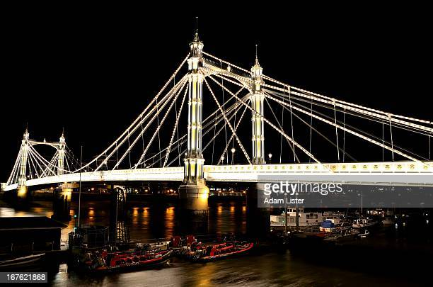 CONTENT] Spanning the River Thames in London the iconic Albert Bridge is illuminated against a black sky at night Boats are moored under the bridge