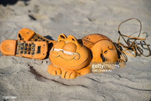 TOPSHOT Spare parts of plastic 'Garfield' phones are displayed on the beach on March 28 2019 in Plouarzel western France after being collected from a...