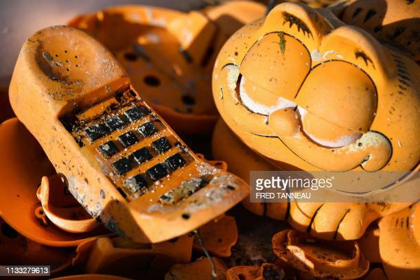 Spare parts of plastic 'Garfield' phones are displayed on the beach on March 28 2019 in Plouarzel western France after being collected from a sea...