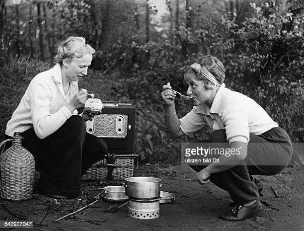 Spare time pictures Two women cooking on a camping stove and listening to a portable radio 1938 Published by 'Hier Berlin' 23/1938 Vintage property...