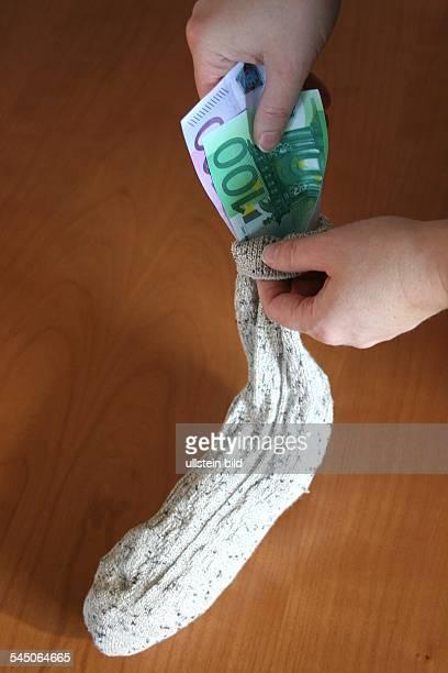 Sparen Sparstrumpf Geldscheine werden in einen Wollsocken gesteckt