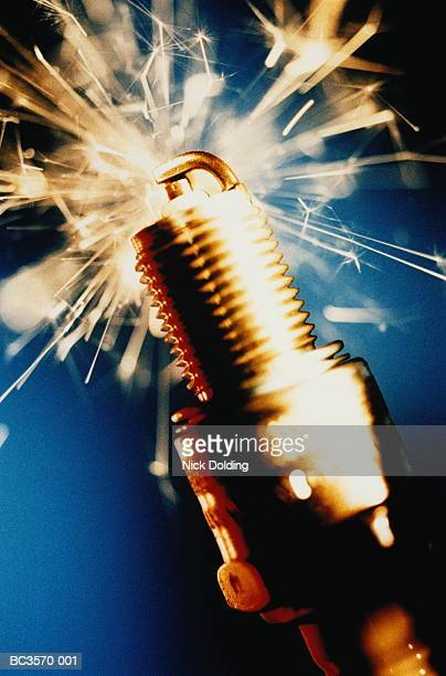 Spark plug surrounded by sparks, close-up