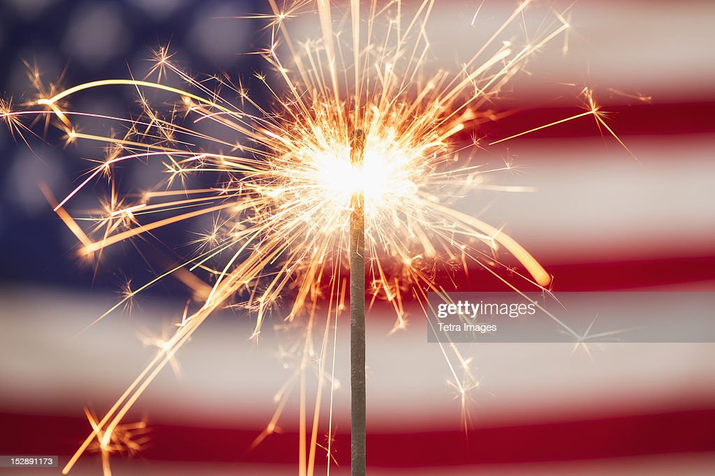 Sparkler and American flag : Stock Photo