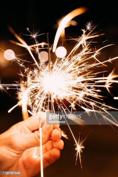 sparkler burning slowly in man hand at night - 4th stock pictures, royalty-free photos & images