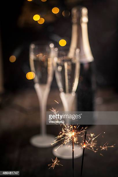Sparkler in front of two champagne flutes and bottle, studio shot