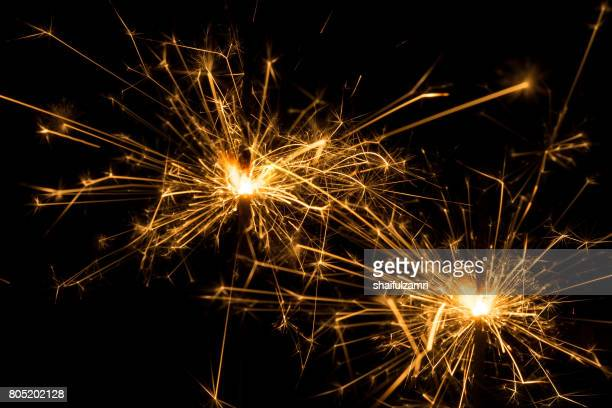 a sparkler is a type of hand-held firework that burns slowly while emitting colored flames, sparks, and other effects. - shaifulzamri imagens e fotografias de stock