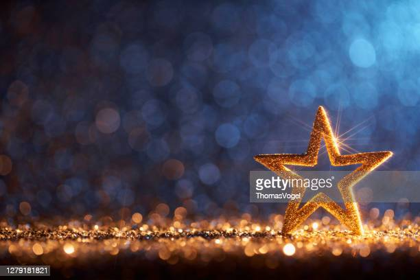 sparkling golden christmas star - ornament decoration defocused bokeh background - weihnachten hintergrund stock-fotos und bilder