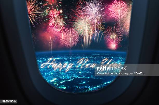Sparkling Happy New Year Text With Firework In Sky Seen Through Airplane Window During Night