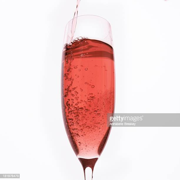Sparkling Rose Wine pouring into Champagne Glass