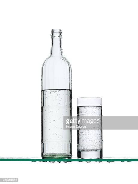 sparkling water in a bottle and a glass - ガラス ストックフォトと画像