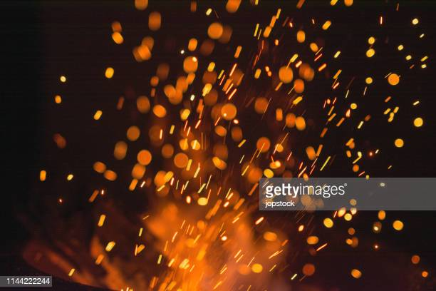 sparks exploding against black background - fire natural phenomenon stock pictures, royalty-free photos & images