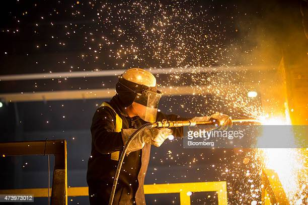 Sparks fly as a worker carries out the process of fettling a ladle in the melt shop at the Celsa Steel UK Ltd steel mill in Cardiff UK on Monday May...