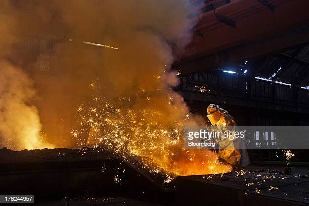 Sparks fly as a worker operates in the blast furnace at ArcelorMittal's steel plant in Ostrava Czech Republic on Monday Aug 26 2013 ArcelorMittal the...