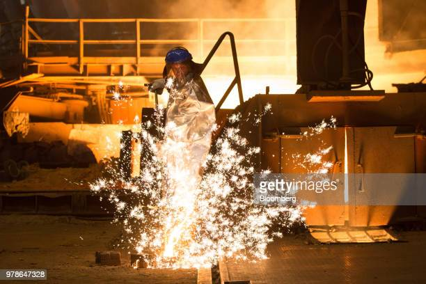 Sparks fly as a worker pours molten cast iron he has collected from a blast furnace at the Novolipetsk Steel PJSC plant operated by NLMK Group in...